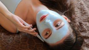 A menina com cosmético mascara sua cara que fala no smartphone Foto de Stock Royalty Free