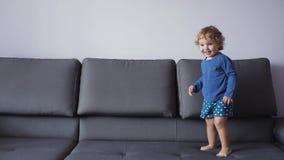 Menina com dança encaracolado do cabelo louro no sofá Movimento lento Roupa azul Sente feliz video estoque