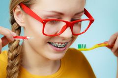 A menina com dentes apoia usando a escova interdental e tradicional fotografia de stock royalty free