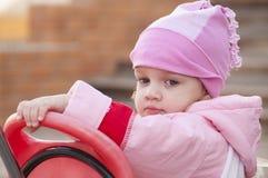 A menina com dois anos olha pensativamente de assento em uma bicicleta Fotos de Stock Royalty Free