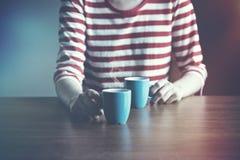 Menina com dois xícaras de café ou chás Fotos de Stock