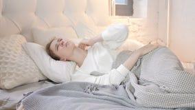 Menina com a dor de pescoço que coloca na cama video estoque