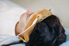 Menina com elétrodos do eeg toda em torno de sua cabeça que tem o exame médico da atividade de cérebro imagem de stock royalty free