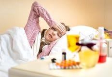 Menina com encontro de alta temperatura na cama e vista no chá Fotografia de Stock Royalty Free
