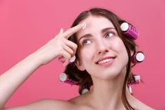 A menina com encrespadores de cabelo põe um creme cosmético sobre a cara, olha ascendente e sorriso Close-up fotos de stock royalty free
