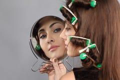 Menina com encrespadores e espelho de cabelo fotos de stock royalty free