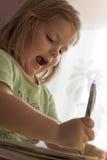 A menina com entusiasmo escreve Imagem de Stock