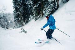 A menina com equipamento especial do esqui é de montada e de salto muito rapidamente na floresta da montanha fotos de stock royalty free