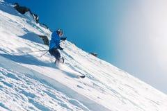 A menina com equipamento especial do esqui está montando muito rapidamente no monte da montanha imagem de stock royalty free