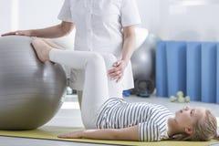 Menina com escoliose e fisioterapeuta imagem de stock