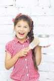 Menina com escova e lata da pintura de encontro ao wa do tijolo Foto de Stock
