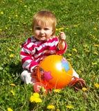 Menina com esfera em uma grama Foto de Stock Royalty Free