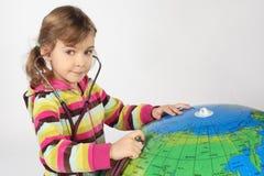 Menina com estetoscópio e o globo inflável grande Foto de Stock Royalty Free