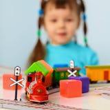 Menina com estrada de ferro do brinquedo Fotografia de Stock