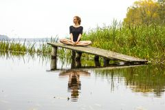 Menina com figura 'sexy' dos esportes no fundo do rio calmo do outono A ioga, meditação, relaxa Fotos de Stock Royalty Free