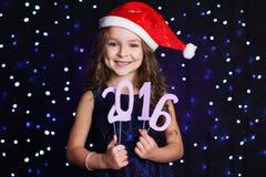 Menina com 2016 figuras de papel, tempo de Santa do Natal Fotografia de Stock Royalty Free