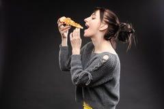 Menina com fome com boca aberta que come a pizza fotografia de stock royalty free