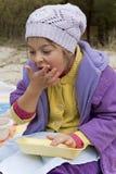 A menina com fome come com mãos Fotos de Stock Royalty Free