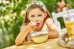 A menina com fome come o muesli para o café da manhã imagem de stock