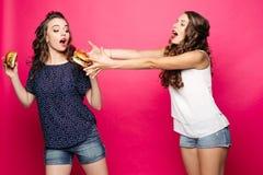 Menina com fome que tenta obter seu hamburguer do ` s do amigo imagens de stock