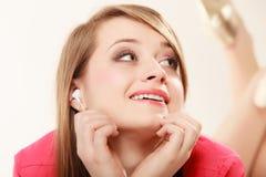 Menina com fones de ouvido brancos que escuta a música Imagem de Stock