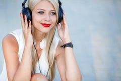 Menina com fones de ouvido em um fundo azul fotografia de stock