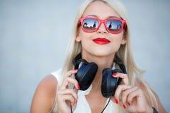 Menina com fones de ouvido em um fundo azul fotos de stock royalty free