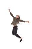 Menina com fones de ouvido que é de dança e de salto ao escutar a música foto de stock royalty free