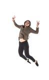 Menina com fones de ouvido que é de dança e de salto ao escutar a música fotografia de stock
