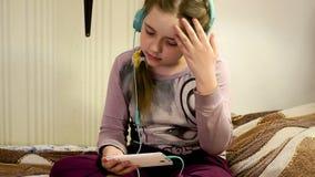 Menina com fones de ouvido que escuta a música do smartphone video estoque