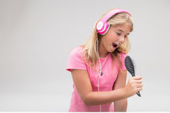 Menina com fones de ouvido que finge ser um cantor Imagem de Stock Royalty Free