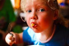 Menina com forquilha e macarrão em sua boca Fotografia de Stock Royalty Free