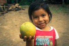 Menina com fruto em Bolívia Fotografia de Stock Royalty Free