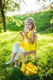 Menina com fruto em um gramado verde imagem de stock