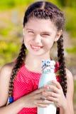 Menina com a garrafa do leite no verão Imagem de Stock
