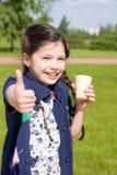 A menina com gelado mostra os polegares acima Imagem de Stock Royalty Free