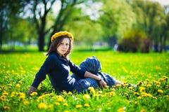 Menina com a grinalda do dente-de-leão amarelo imagens de stock royalty free