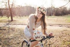 A menina com a grinalda na cabeça pela bicicleta Fotografia de Stock