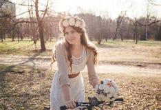 A menina com a grinalda na cabeça pela bicicleta Imagens de Stock