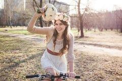 A menina com a grinalda na cabeça pela bicicleta Imagem de Stock Royalty Free
