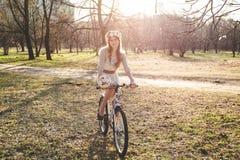 A menina com a grinalda na cabeça pela bicicleta Imagens de Stock Royalty Free