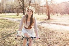 A menina com a grinalda na cabeça pela bicicleta Imagem de Stock