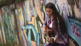 A menina com a guitarra contra uma parede com video estoque