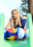 Menina com inflamento de bolas na corrediça Fotografia de Stock