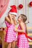 A menina com interesse sussurra algo a uma outra menina em um tampão dos anos novos Fotografia de Stock