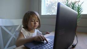 A menina com interesse usa o portátil que senta-se na tabela Tiro da zorra filme