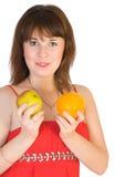 Menina com laranja e maçã nas mãos Foto de Stock Royalty Free