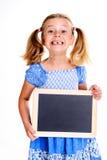 Menina com a largura do espaço que mostra um quadro-negro pequeno Fotos de Stock Royalty Free