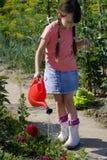 Menina com lata molhando Imagens de Stock