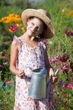 Menina com a lata molhando do metal no jardim do verão Foto de Stock